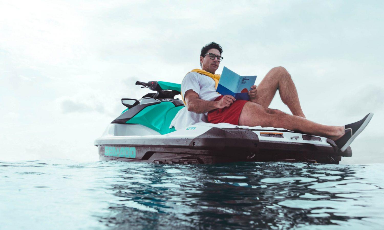 Man reading a book from the Sea-Doo GTI back swim platform
